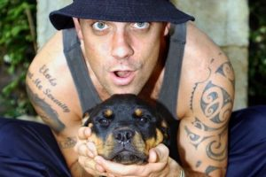 Famous UK singer Robbie Williams posing with his rottweiler